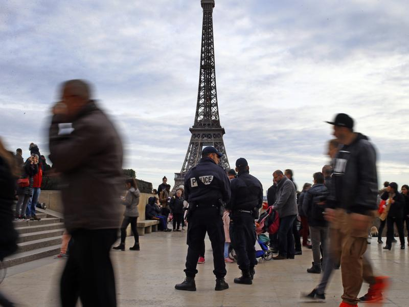 French Police officers stand guard amid tourists at Trocadero Plaza next to the Eiffel Tower in Paris. France strengthens security measures ahead of unusually tense New Year's eve celebrations in Paris after November attacks that left 130 dead and hundreds injured. (AP Photo/Francois Mori)