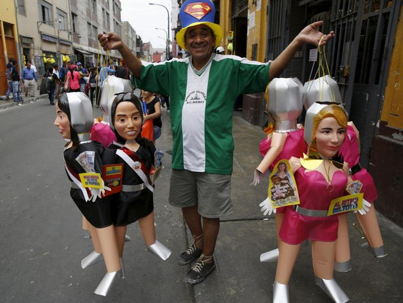 A man sells effigies of first lady Nadine Heredia and of Yahaira, a dancer and girlfriend of Peru's soccer player Jefferson Farfan, in a market in Lima, Peru. Peruvians traditionally burn effigies of popular figures from the past year as part of New Year's celebrations.  (REUTERS/Mariana Bazo)