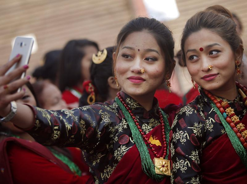 Nepalese Gurung community women wearing traditional attire take their selfie at a parade to mark their New Year known as