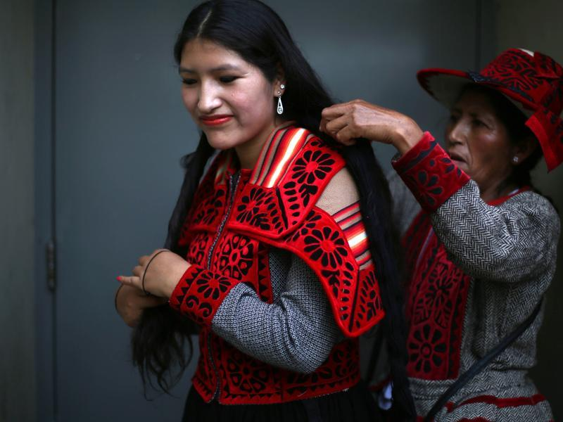 Andean indigenous dancer Waira Sacsi is helped with her hair by her mother Flor before the start of the 'Takanakuy' fighting ritual on the outskirts of Lima, Peru on Christmas day. Dancers open the event to traditional Andean music known as 'Huaylia'. (AP)