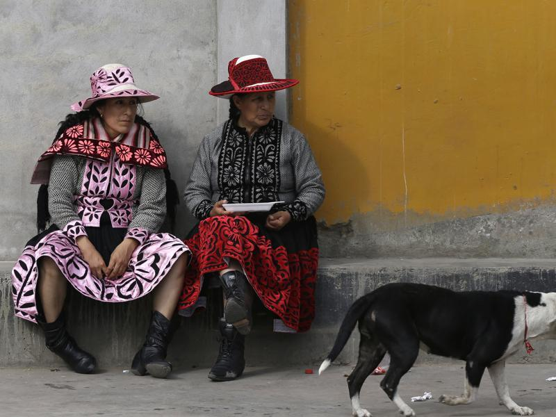 In this December 25, 2015 photo, dancers wearing traditional Andean dresses eat lunch before the 'Takanakuy' ritual fighting event on the outskirts of Lima, Peru. During the fights, women sing 'Huaylia' music accompanied by accordions, harps, violins and mandolins. The lyrics, in Quechua, include such lines as 'Child, fear not when rivers of blood flow'. (AP)