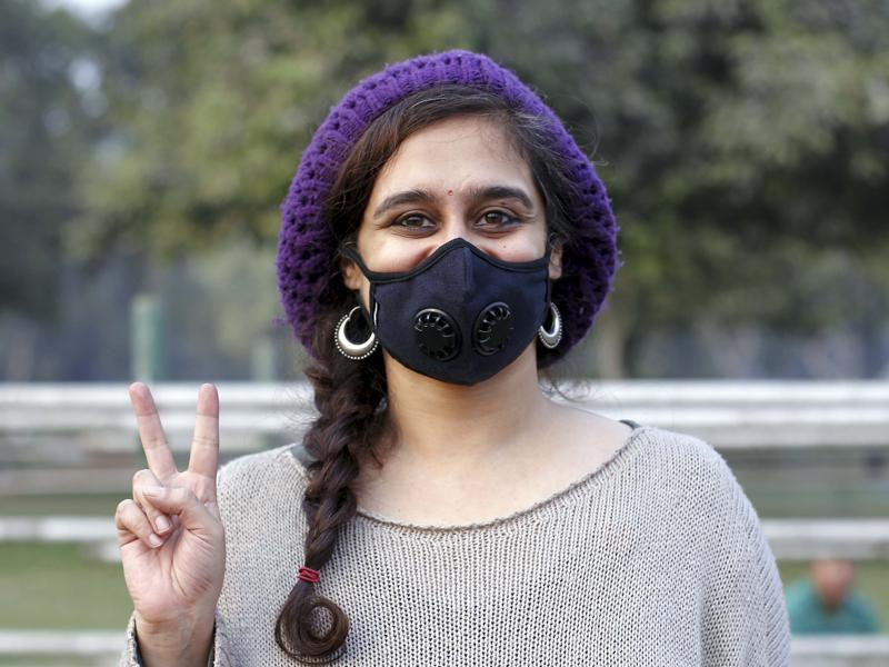 A girl  poses for a photo while attending the campaign against pollution at India Gate. (Ravi Choudhary/ Hindustan Times)