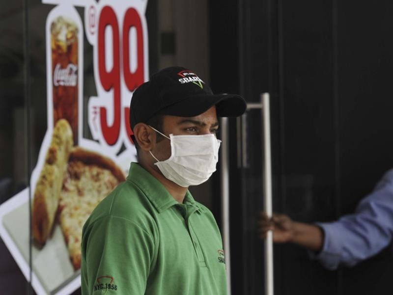 A restaurant worker wearing a  mask at work to protect himself from air pollution in Connaught Place. (Saumya Khandelwal/ Hindustan Times)