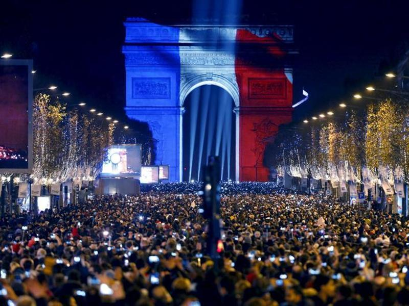 Revellers gather near the Arc de Triomphe which was lit with the blue, white and red colours of the French flag on the Champs Elysees Avenue in Paris. (Reuters)