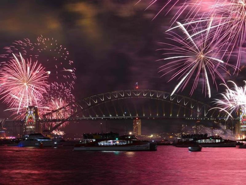 New Year's Eve fireworks illuminate Sydney's iconic Harbour Bridge during the traditional early family fireworks show held before the main midnight event on December 31. (AFP Photo)