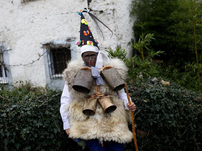 A man dressed in sheepskins with jingling bells to make noise, and so-called Zamarraco (warriors of the good), poses for a photograph during the Vijanera festival, in the small village of Silio, northern Spain, Sunday, January 3, 2016. The Vijanera masquerade, of pre-Roman origin, is the first carnival of the year in Europe symbolising the triumph of good over evil and involving the participation of crowds of residents wearing different masks, animal skins and brightly coloured clothing with its own complex function and symbolism and becoming the living example of the survival of archaic cults to nature.  (AP)