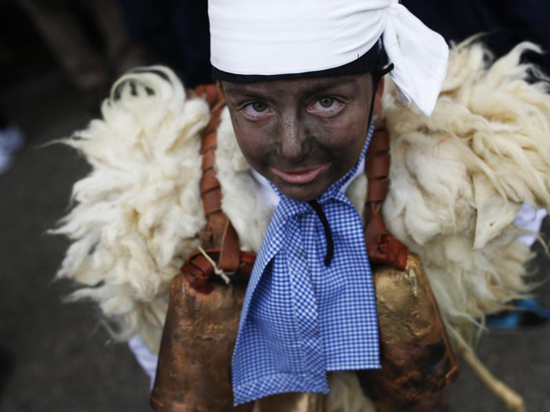 A young boy dressed in sheepskin with jingling bells to make noise poses for a photograph during the Vijanera Festival, in the small village of Silio, northern Spain, Sunday, January 3, 2016. (AP)