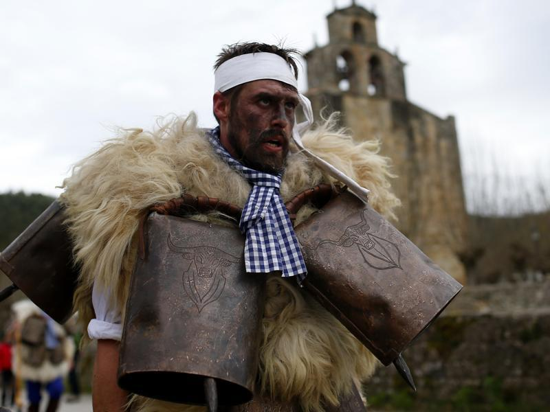 A man, so-called Zamarraco, dressed in sheepskins with jingling bells to make noise, marches with others during in Silio, northern Spain, Sunday, January 3, 2016. (AP)