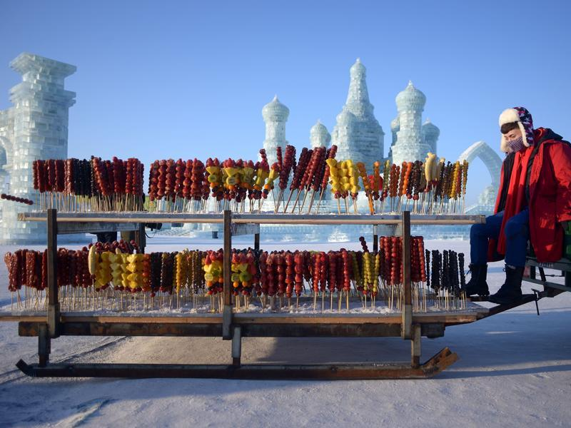 A vendor selling candied haws waits for customers at the China Ice and Snow World before the opening ceremony . (AFP)