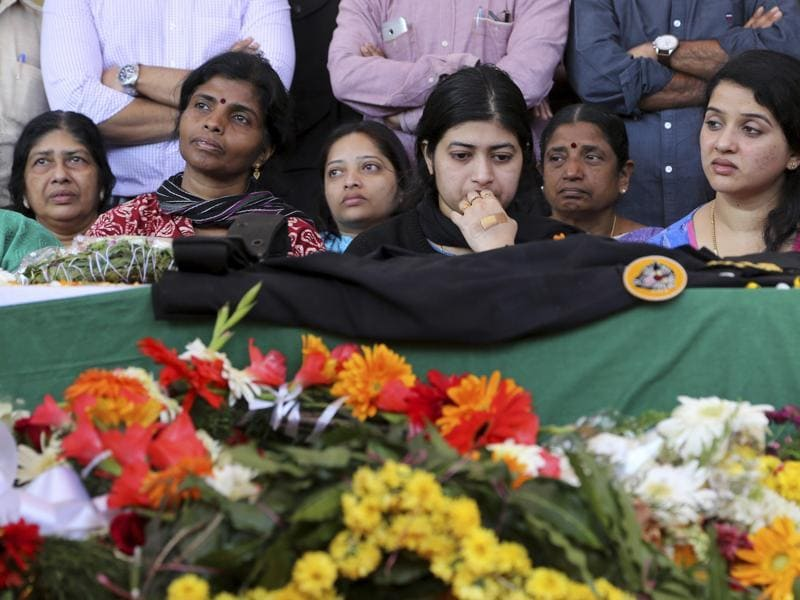 Radhika, center looks at the coffin of her husband and National Security Guard commando, Niranjan Kumar, who was among those killed in the attack on the Pathankot air force base after the body was brought to Bangalore. (AP)