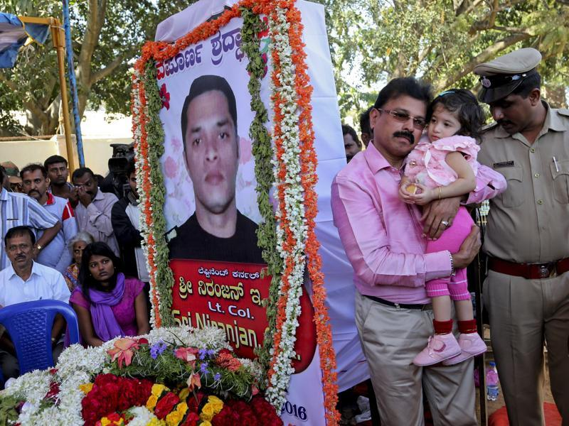 A relative carries Vismaya, daughter of India's National Security Guard commando Niranjan Kumar, portrait seen, who was among those killed in the attack on the Pathankot air force base, next to his coffin placed for public viewing, in Bangalore. (AP)