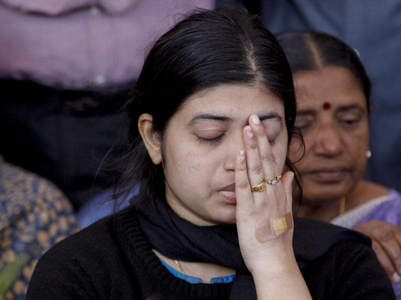 Wife Radhika, wipes her face as she sits next to the coffin of her husband and India's National Security Guard commando, Niranjan Kumar, who was among those killed in the attack on the Pathankot air force base after the body was brought to Bangalore. (AP)
