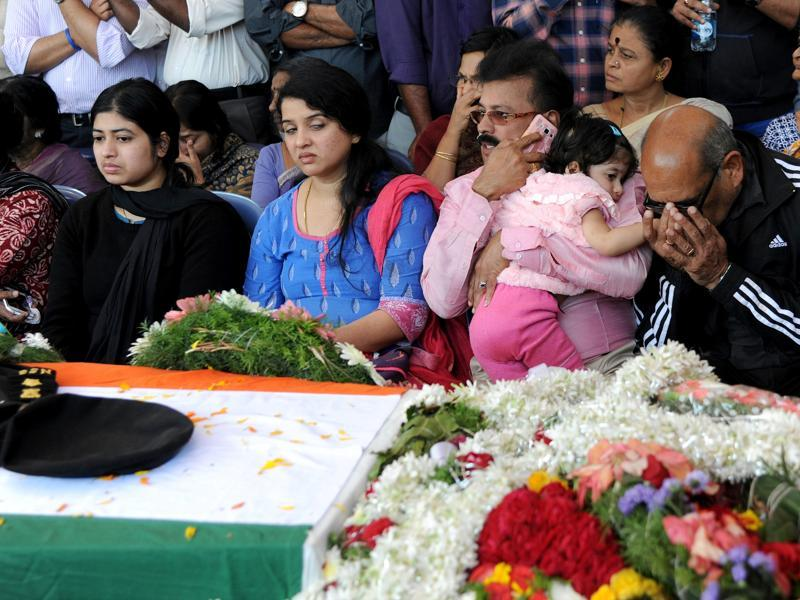 EK Sivaranjam (R), father of slain lieutenant colonel Niranjan Kumar, who died while defusing a grenade at the scene of a terror attack in Pathankot, his daughter-in-law, KG Radhika (L) and her two year-old daughter, Vismaya (2R), mourn with relatives on the arrival of Kumar's mortal remains at his residence in Bangalore. (AFP)