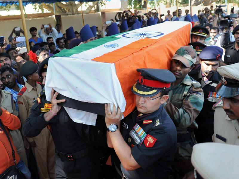 Army personnel carry the mortal remains of Lt Col Niranjan Kumar at his home in Bengaluru on Monday.  (PTI)
