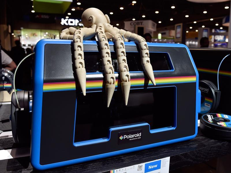 The wooden octopus-like figure on displayed was printed by Polaroid 3D Printer ModelSmart 250S that it now sits on top of. (AFP)