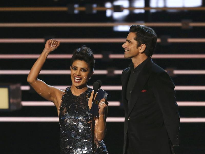 Priyanka Chopra of Quantico and John Stamos of Grandfathered accept their awards for favourite actor and actress in a new TV series before presenting the award for favourite movie at the People's Choice Awards 2016 in Los Angeles. (REUTERS)