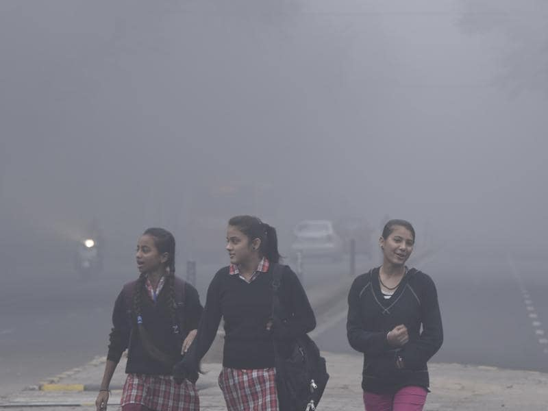 Girls on their way to school on Friday morning. Despite the fog, the city is going through its warmest winter in eight years. (Arvind Yadav/HT photo)