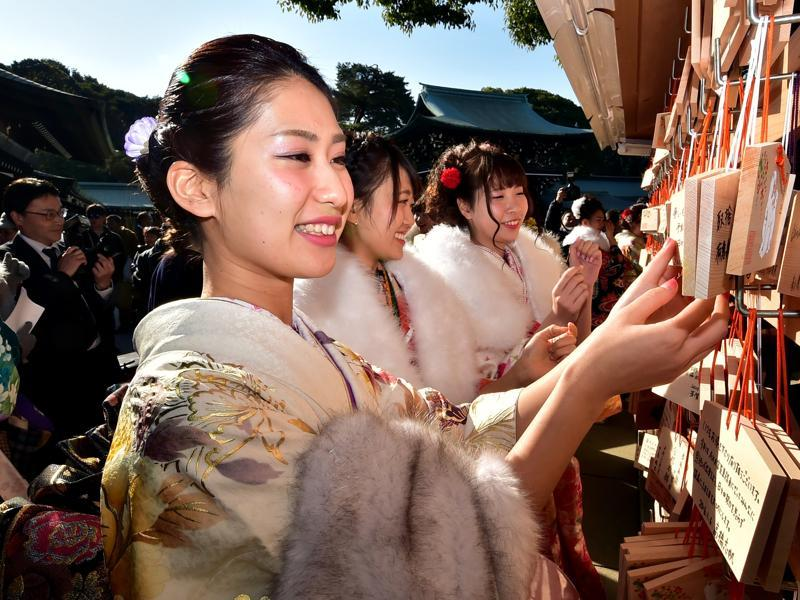 Female tour guides dressed in traditional kimonos hang 'ema', or votive tablets, with their written wishes at the Meiji shrine after attending a purification ceremony. (AFP)