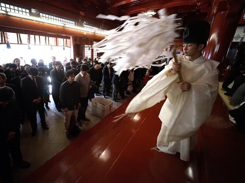 A Shinto priest blesses businessmen for the prosperity of their firms during a ceremony at Kanda Myojin Shrine in Tokyo, on the first business day of the year in Tokyo, Monday, January 4. (AP)