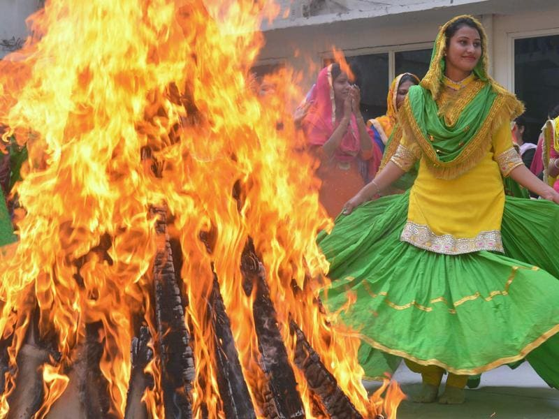 College women clad in traditional Punjabi dress performing 'giddha' (folk dance) around a bonfire during Lohri celebrations in Amritsar. (AFP Photo)