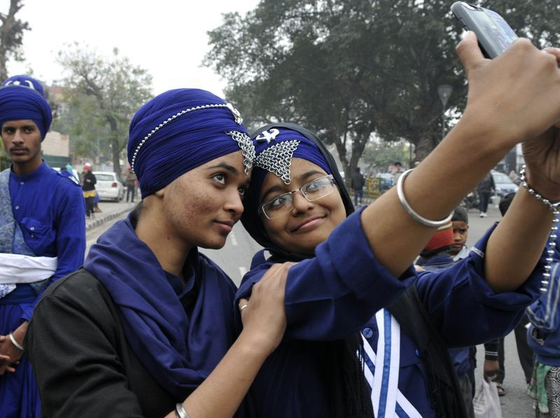Devotees taking a moment off to click a selfie during the religious procession (Nagar Kirtan), ahead of Guru Gobind Singh's tenth birth anniversary in SAS Nagar on Thursday. (Gurminder Singh/HT Photo)