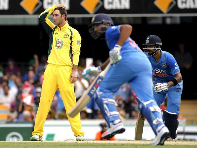 Australia's Glenn Maxwell (L) reacts after being hit for a boundary by Rohit Sharma (C), as he runs between the wickets with teammate Virat Kohli. (Reuters Photo)