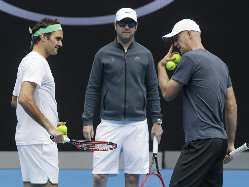 Switzerland's Roger Federer, left, talks with his coaches Ivan Ljubicic right, and Severin Luthi during a practice session ahead of the start of the Australian Open. (AP Photo)