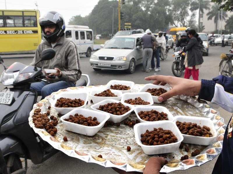 Sewadars distribute prasad (sacred food) to commuters as a part of the Nagar Kirtan.  (Keshav Singh/HT Photo)