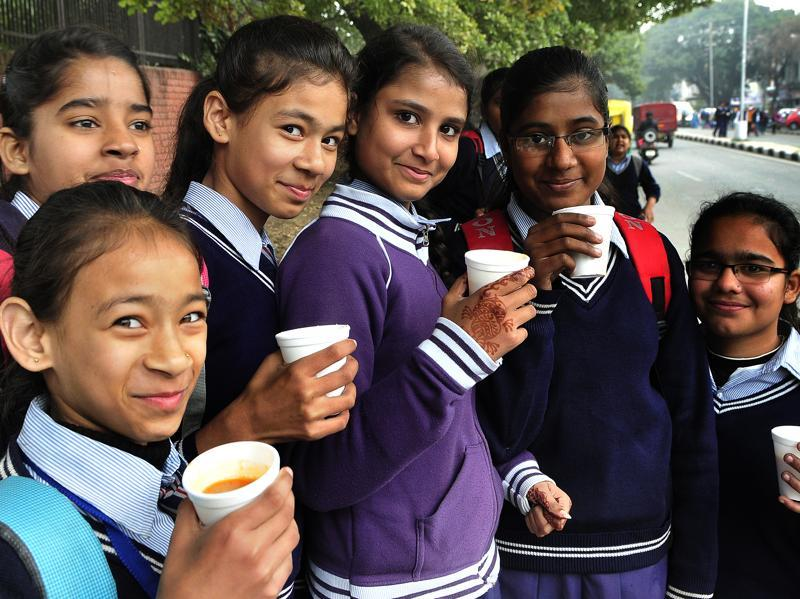 School kids enjoy tea and pose for pictures on Thursday.  (Keshav Singh/HT Photo)