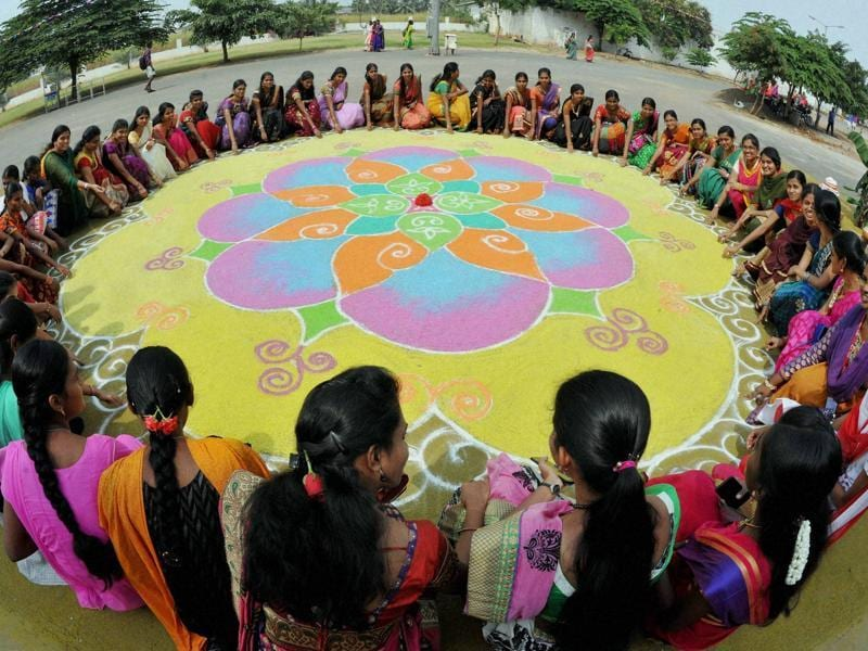 College students making a Kolam on the occasion of Pongal festival in Coimbatore on Wednesday. (PTI)