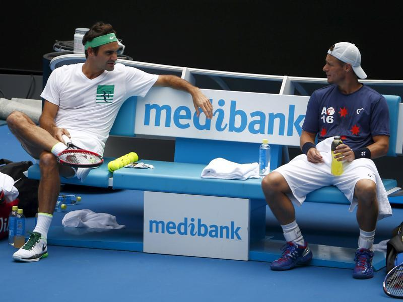Federer talks to Australia's Lleyton Hewitt as they take a break during a practice session. (Reuters Photo)