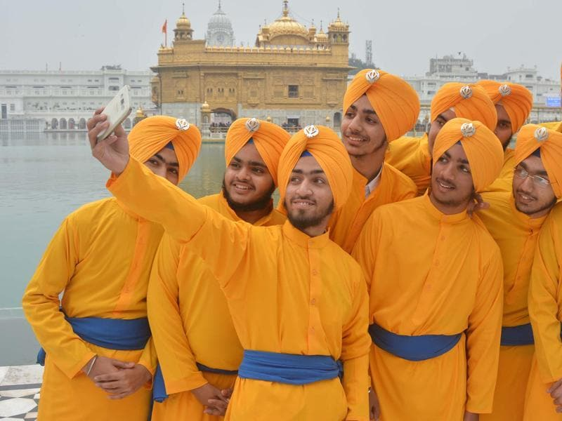Young Sikh devotees  taking a selfie on the eve of  birth anniversary of the tenth Sikh guru at Golden Temple in Amritsar.  (Sameer Sehgal/HT )