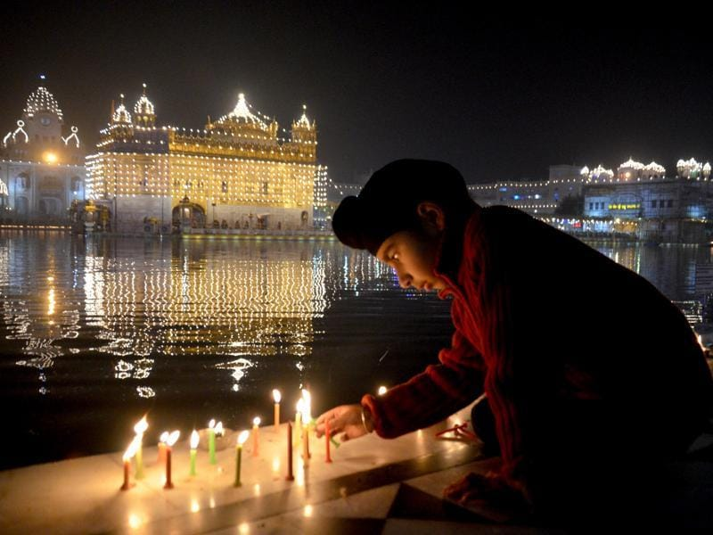 A child lighting candles at the Golden Temple on the occasion of birth anniversary of Guru Gobind Singh in Amritsar on Saturday.  (Sameer Sehgal/HT Photo)