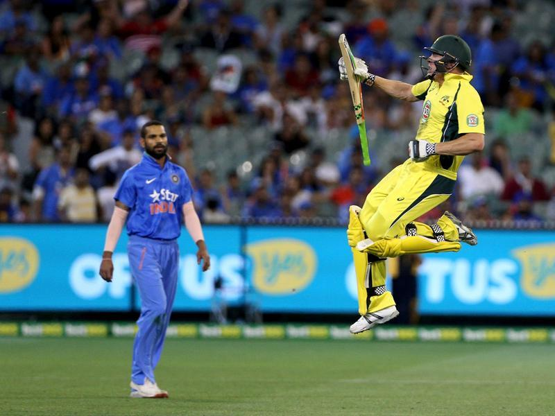 Australia's James Faulkner celebrates hitting the winning runs as India's Shikhar Dhawan watches during their One Day cricket match at the Melbourne Cricket Ground. (REUTERS)