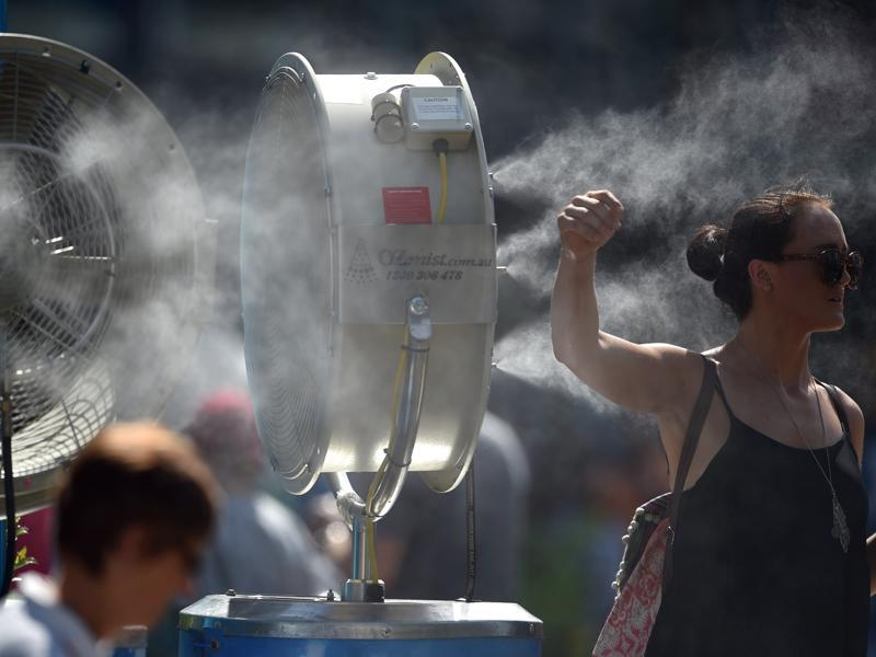 A woman cools herself down as she stands next to a mist fan on day one of the 2016 Australian Open. (AFP Photo)