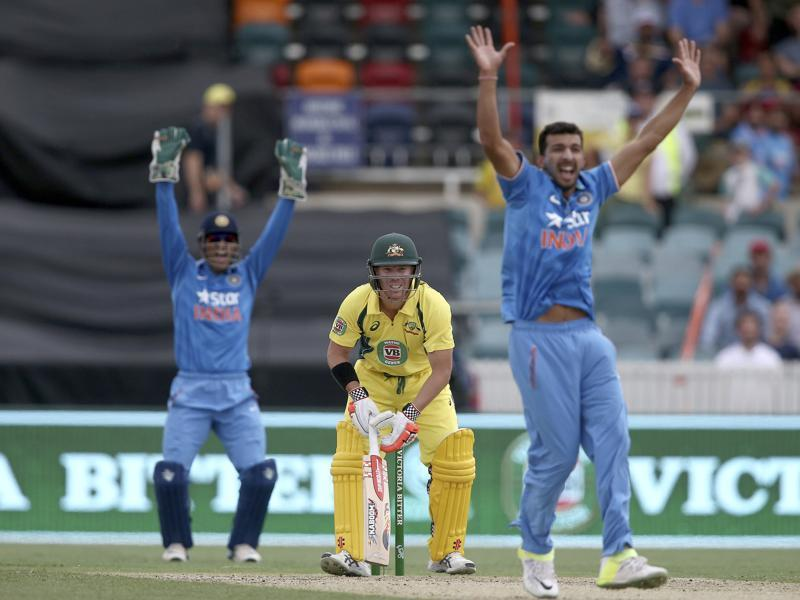 Australian batsman David Warner, center, watches as Rishi Dhawan, right, and MS Dhoni appeal for an LBW decision. (AP Photo)