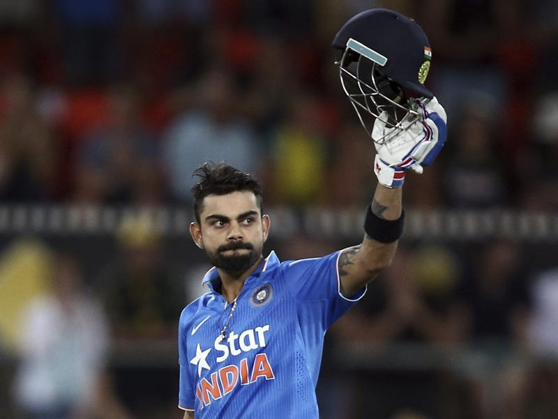 Virat Kohli holds up his helmet as he celebrates hitting a century. (AP)