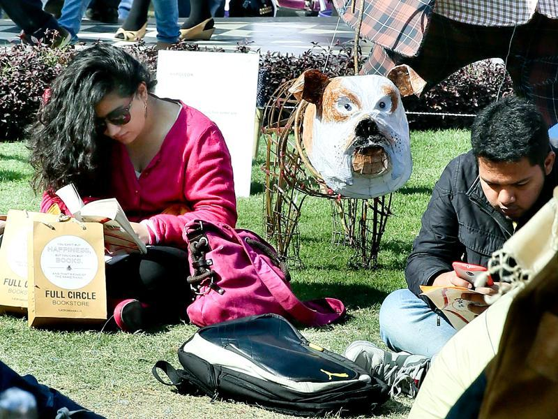 Visitors make the most of a sunny day as they read books and enjoy the sunshine between sessions on the first day of JLF. (Sanjeev Verma/ HT Photo)