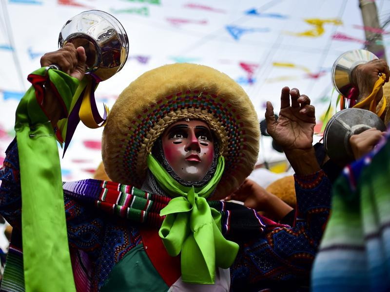 The festivities end at a church where stands an old tree, said to represent 'tree of life' and has its roots in the pre-Christian era. A man dances during the celebration of Parachicos in Mexico. (AFP)