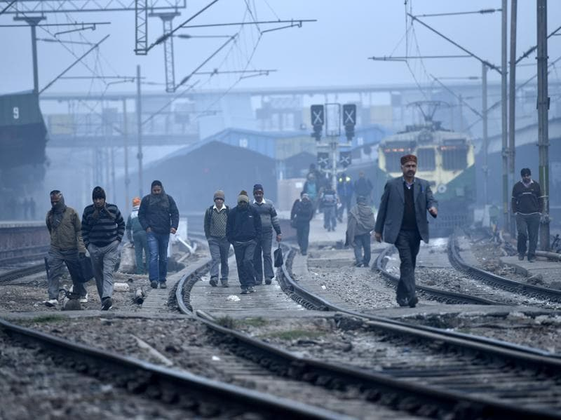 People cross tracks near New Delhi railway station where fog has delayed many trains.  (Arun Sharma/ HT Photo)