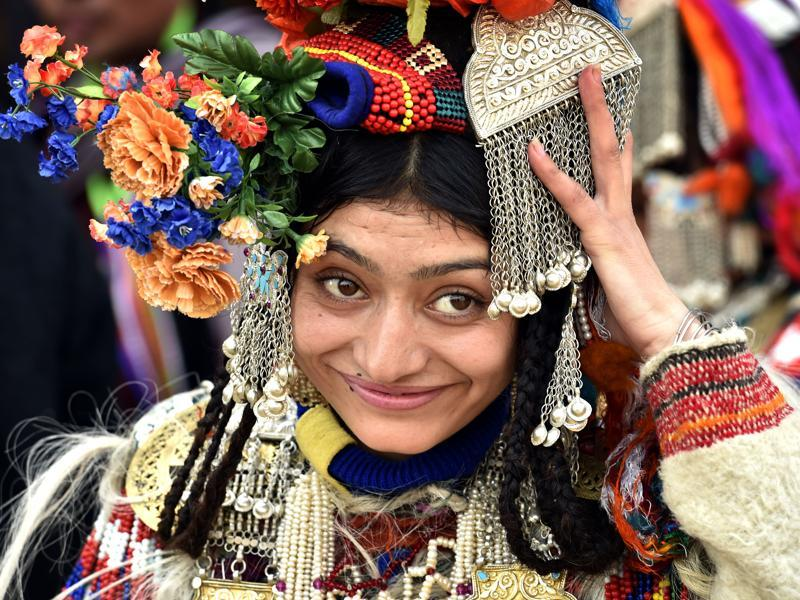A woman dressed in the traditional attire of Jammu and Kashmir's Ladakh region adjusts her headgear. (Ajay Aggarwal/ HT Photo)