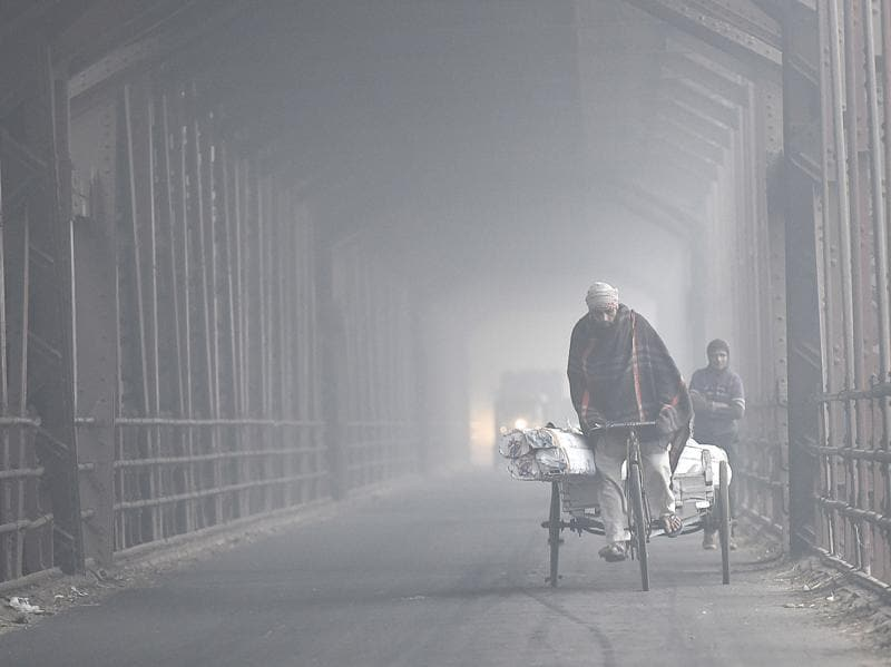 No matter fog or not, cold or warmth, some routines continue, like  these people on their daily schedule pictured on the Old Bridge in Delhi's Yamuna Vihar. (Raj K Raj / HT Photo)