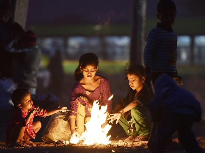 Shelter or not, warmth is necessary: Children sit around a bonfire at Turkman Gate in New Delhi as the mercury in the Capital drops. (Raj K Raj / Hindustan Times)