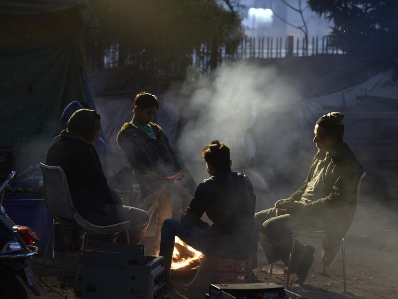 Relief for some, stifle for many: People warm themselves around a bonfire at Turkman Gate in New Delhi. The impact of the smoke on the air quality is unchecked. (Raj K Raj / HT Photo)