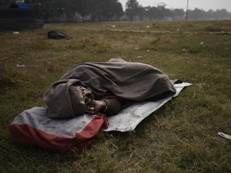 'The sky is my ceiling.The grass is my bed':  A man sleeps at a park on a cold winter morning in the walled city of New Delhi. (Ravi Choudhary/HT Photo)