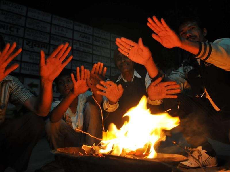As temperature in the city drops, people take some guard against cold as they gather around a bonfire. (Shankar Mourya/ HT Photo )