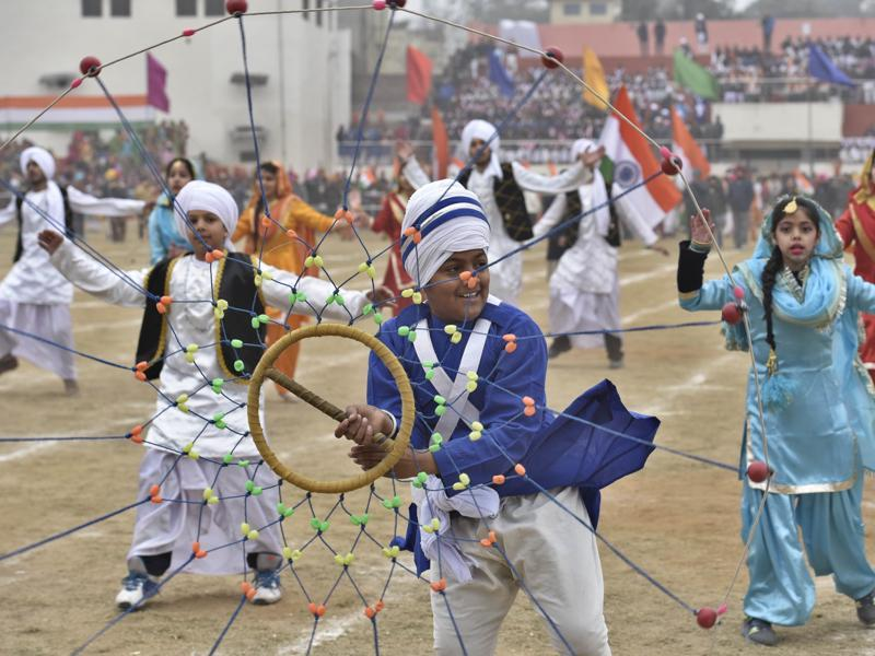 A school student performs gatka while others dance at Guru Nanak Dev Stadium, Amritsar on Saturday. (Gurpreet Singh/HT Photo)