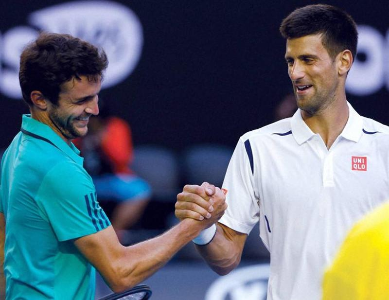 Novak Djokovic shakes hands with Gilles Simon after winning their fourth round match at the Australian Open. (AP Photo)