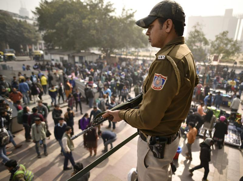 A security personnel stands on guard amid a busy market in New Delhi. (HT Photo)