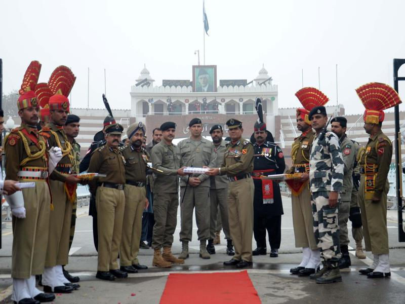 Border Security Force (BSF) DIG Sumer Singh (R) along with other officials offer sweets to Pakistan Rangers wing commander Bilal Ahmed (L) on the occasion of 67th Republic Day celebration at Wagah Border in Attari on Tuesday.  (Sameer Sehgal/HT Photo)